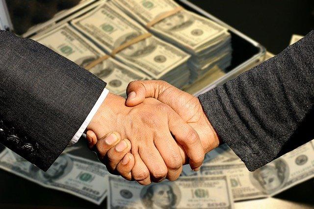 podání rukou s pozadím peněz