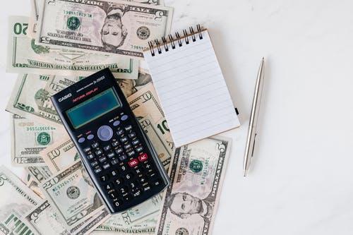 kalkulačka a bloček, peníz